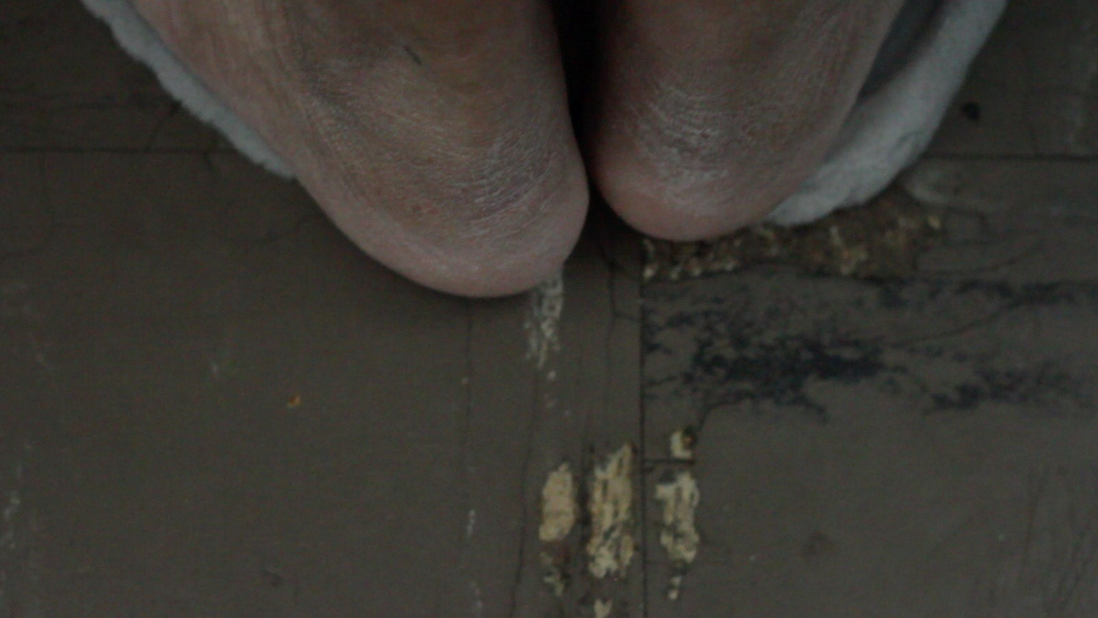 A still from Akinola Davies' film Untitled. The heels of two feet on concrete floor.