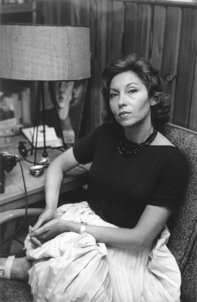 A black and white photo of Clarice Lispector sat on a chair looking up at the camera