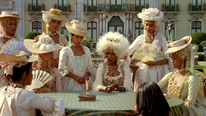 A still from Gullivers Travel, showing women sat at a table in period dress, with white wigs on