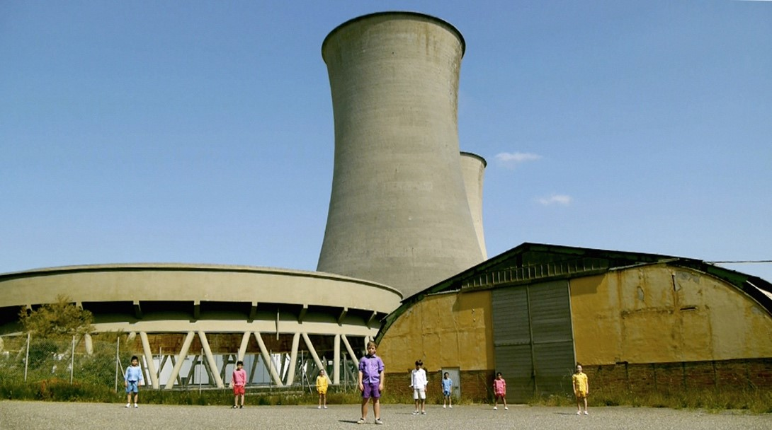 A still from Mikhail Karikis' film 'Children of Unquiet'. It shows children stood in front of a disused power plant.