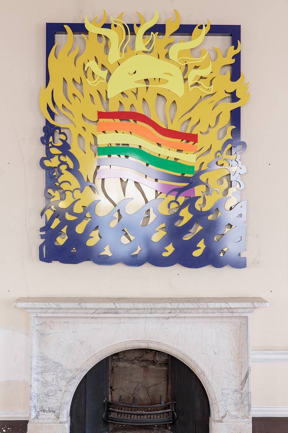 Installation view of UK Gay Bar Directory. The image shows an artwork on the wall above a fireplace, depicting smiling sun and a rainbow flag.