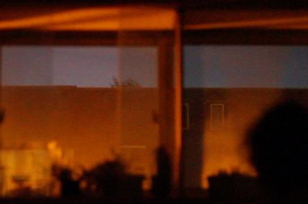 A still from Akinola Davies' film Untitled. Depicts interior reflections against a window and sky.