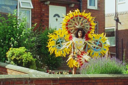 An image of a woman stood in a bright, colourful yellow, sun-like costume in a front garden.