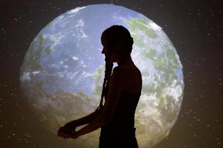 A woman (Anna Mikkola) standings in front of a projection of the world, as seen from space