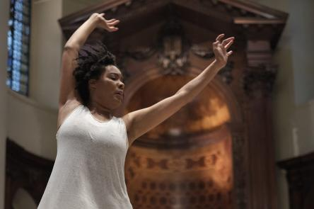 A photo of Elaine Mitchener performing. Elaine stands in a grand-looking auditorium or church, with her arms held high as she conducts music.