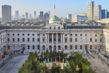 Forest for Change at Somerset House. Green leafy trees fill the courtyard. In the background you can see the London skyline and blue skies.