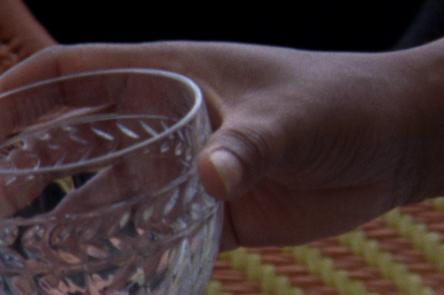 A still from Ana Vaz's Occidente. It shows a hand holding a crystal cut glass.