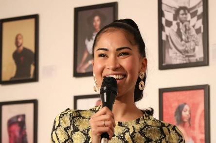 A photo of Swarzy smiling with a microphone in her hand. She stands in front of a wall of framed photos of Black creatives at an exhibition created by Swarzy, entitled Too Much Source.