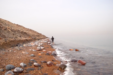 A still from a work by Dina Mimi. A small lone figure stands at the centre of shot. They are stood on a steep, pebble laden beach, with the sea on their right. It is overcast and the figure is turned away from the camera, and looks to be moving away.