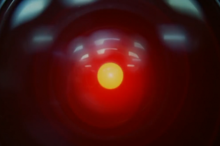 A still from 2001: A Space Odyssey, used as a reference for not/nowhere's episode of Transmissions. A close up of HAL. An ominous red light sits at the centre of a camera lens, unblinking.