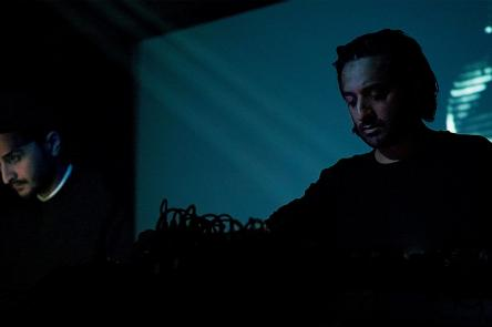 A photo of Paul Purgas and Imran Perretta performing together (as AMRA, their audiovisual collaboration)