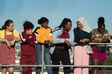 A still from Rocks. A group of girls on a rooftop, smiling.