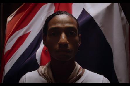 A still from Gareth Pugh's film 'Soul of a Movement'. It shows a person stood infront of a Union Jack flag.