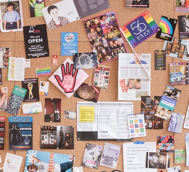 Installation view of UK Gay Bar Directory. The image shows an artwork presenting flyers and flags from different gay bars.