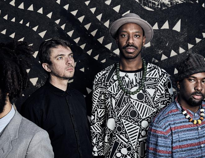 A photo of the band Sons of Kemet. Four men, stood against a patterned black and white backdrop.