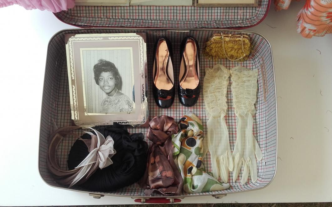 A suitcase containing shoes, clothing accessories and a framed portrait, belonging to a Windrush generation migrant