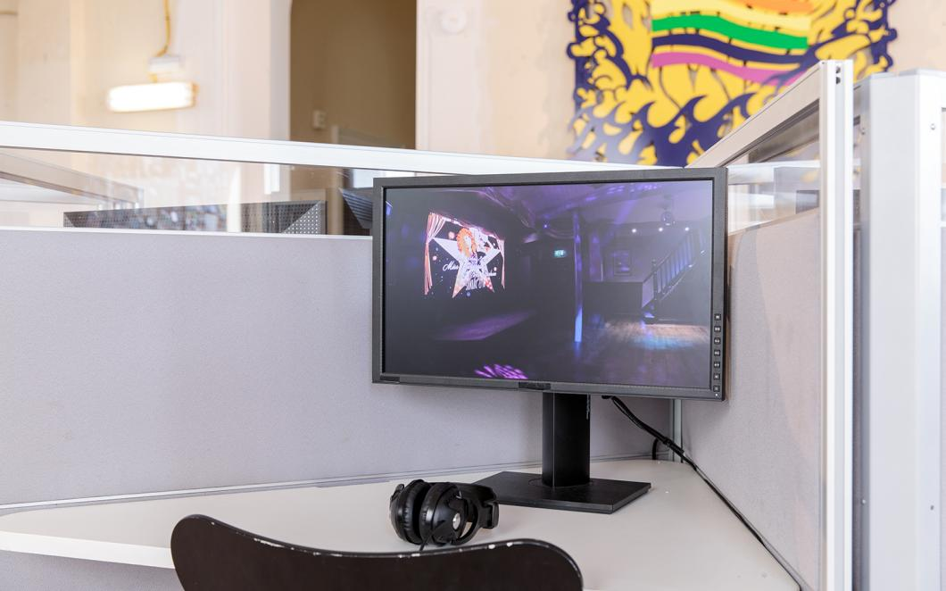 Installation view of UK Gay Bar Directory. The image shows a computer and screen at a desk. Behind there is an artwork on the wall showing a smiling sun and a rainbow flag.