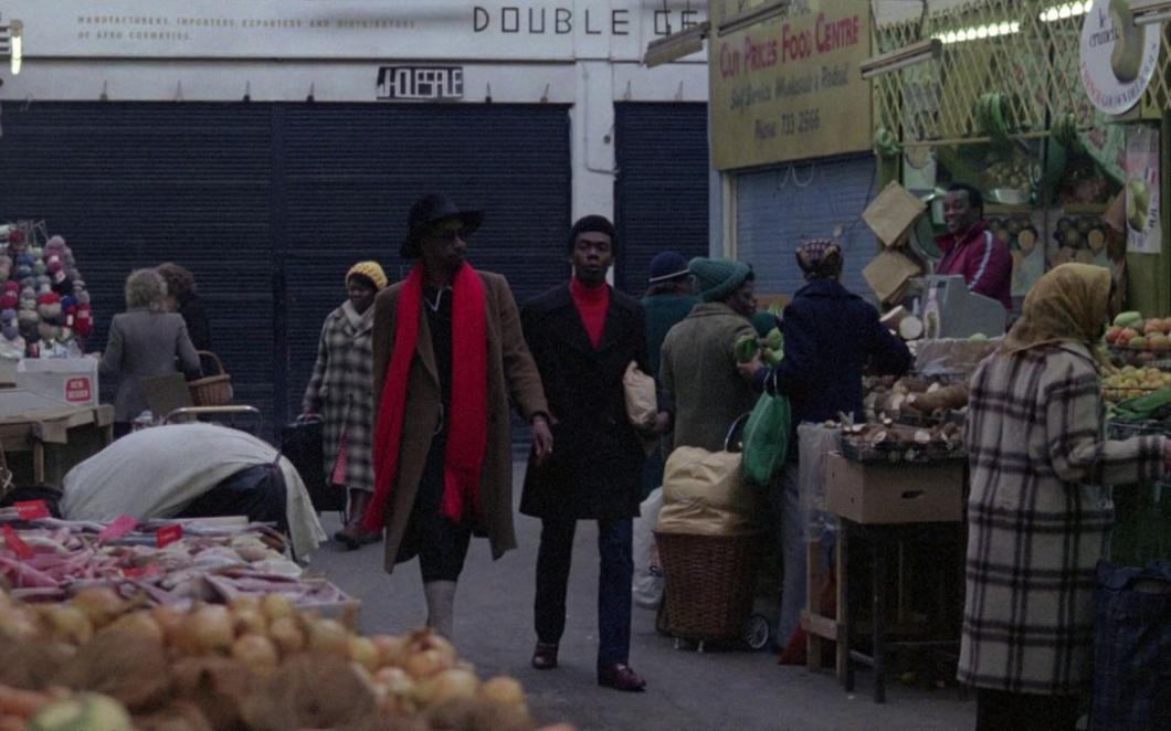 A still from the film Babylon showing two Black men walking through a covered market in South London