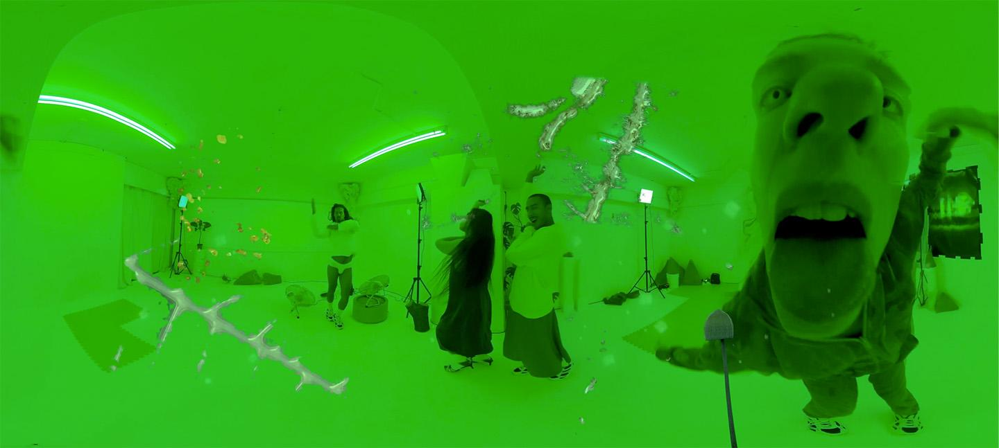 A still image from Adham Framawy's film. It shows a room that lit is entirely green with four people inside, dancing.