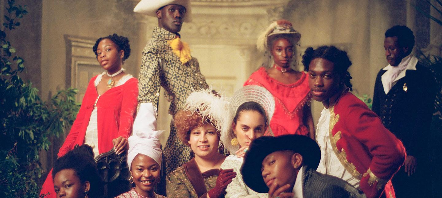 A still from an Akinola Davies Jr. film. It shows young people of colour dressed in Regency period dress, wearing suits with feathers in their hats and long sweeping gowns. They are all looking to camera and smiling.