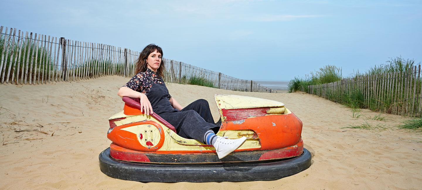 Anna Meredith, Bumps Per Minute album cover shows Anna sitting in a dodgem amongst some sand dunes © Mike Massaro