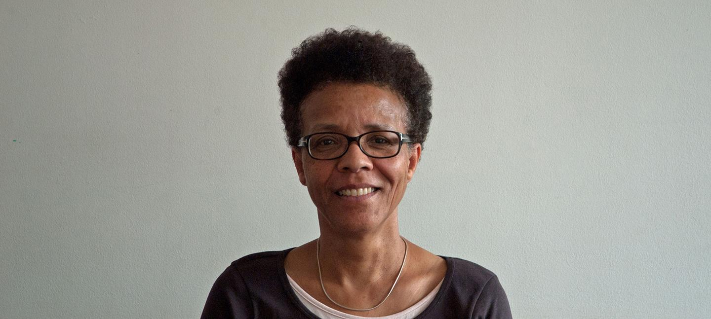 A photo of Gail Lewis. A Black woman wearing glasses with short cropped hair. Gail is looking directly to the camera and has a kind smile.
