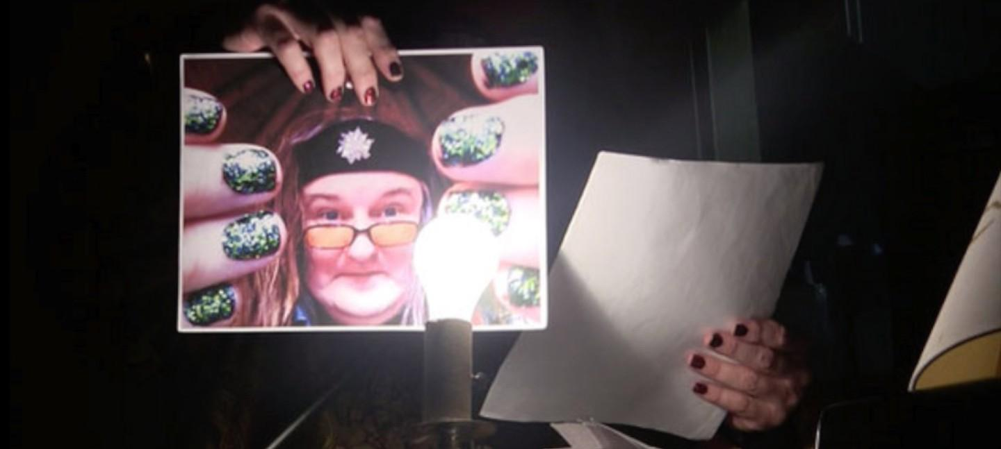 Someone holding up a photo of a woman in a headband and glasses to the camera, with a lit light bulb in front.