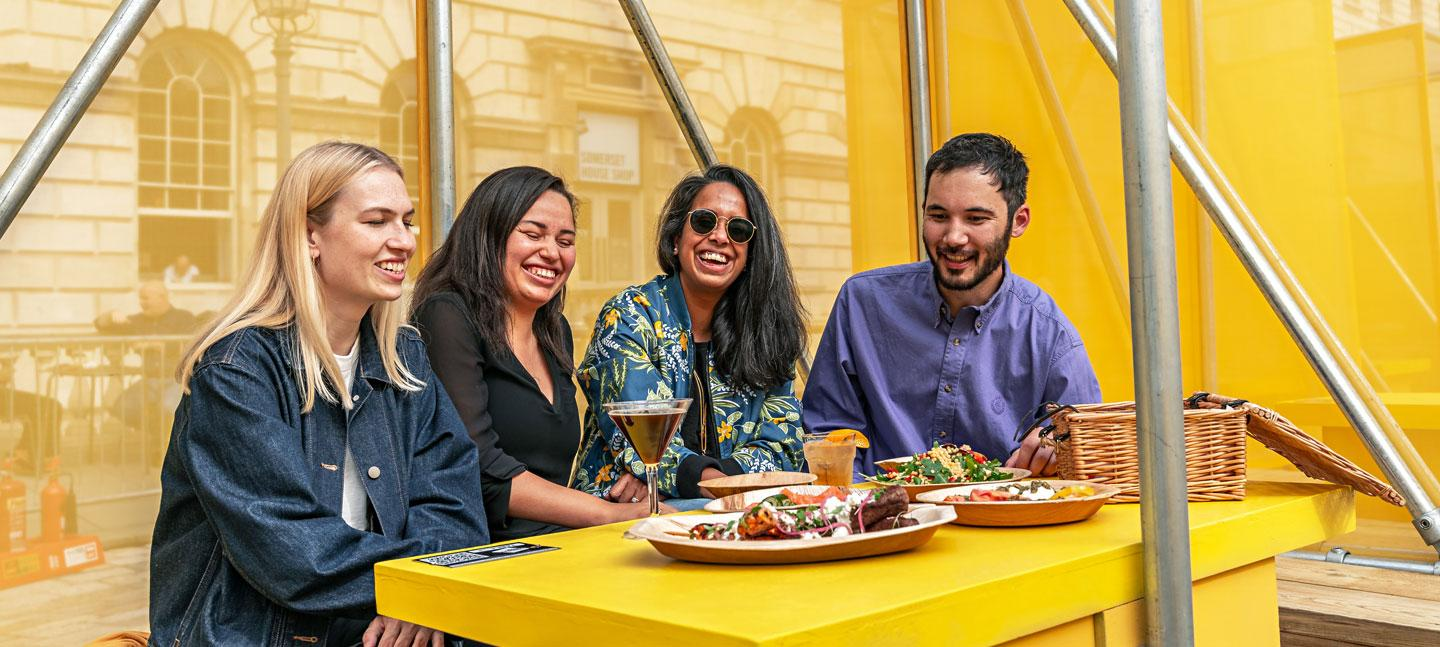 A group of four enjoying food and drink at a colourful booth designed by Yinka Ilori, located in the courtyard at Somerset House