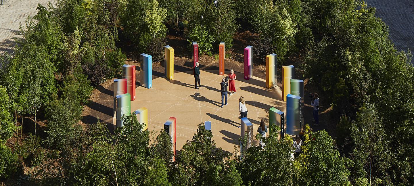 An aerial view of Forest for Change, focussing in on the installation at its centre. Lots of coloured obelisk shapes in a clearing, surrounded by a forest of trees.