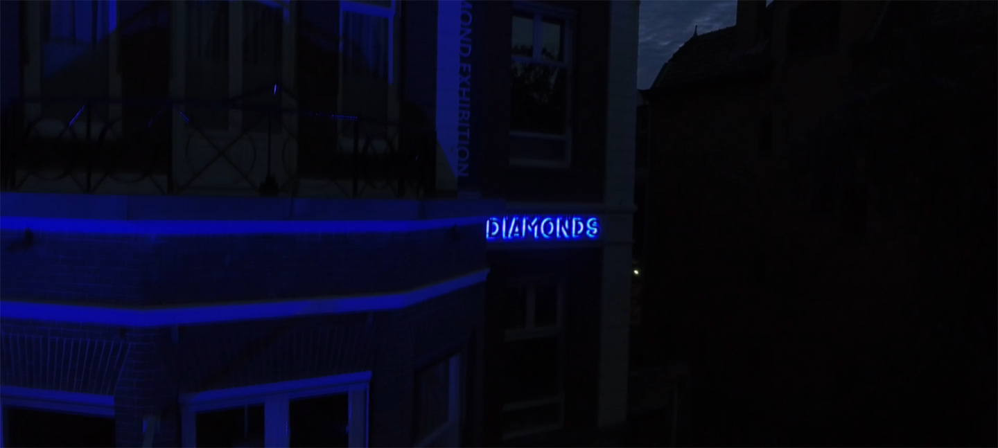 A still from Gerda Paliušytė's film. It depicts a blue neon sign on a building that says 'diamonds'