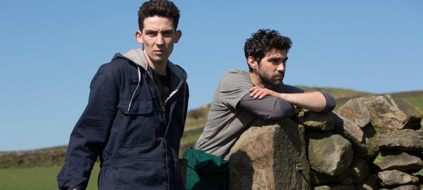 Film still of two men leaning on a fence