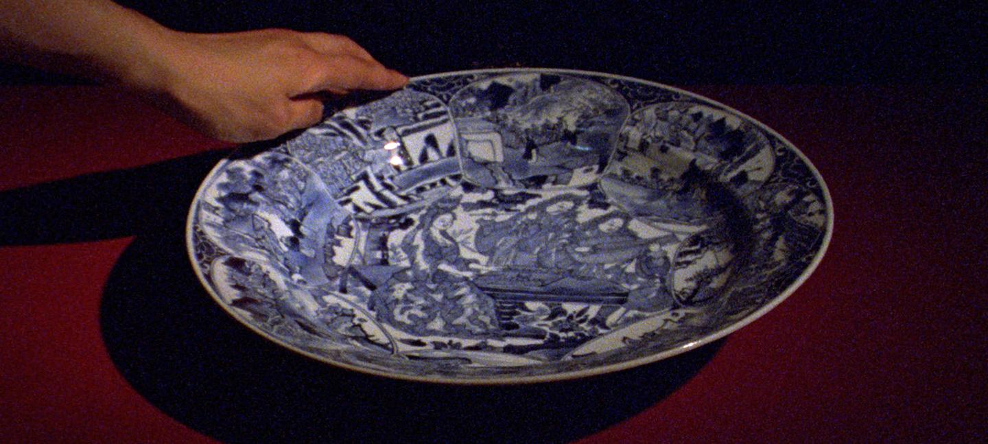 A still from Occidente by Ana Vaz. It shows a hand holding a china plate.
