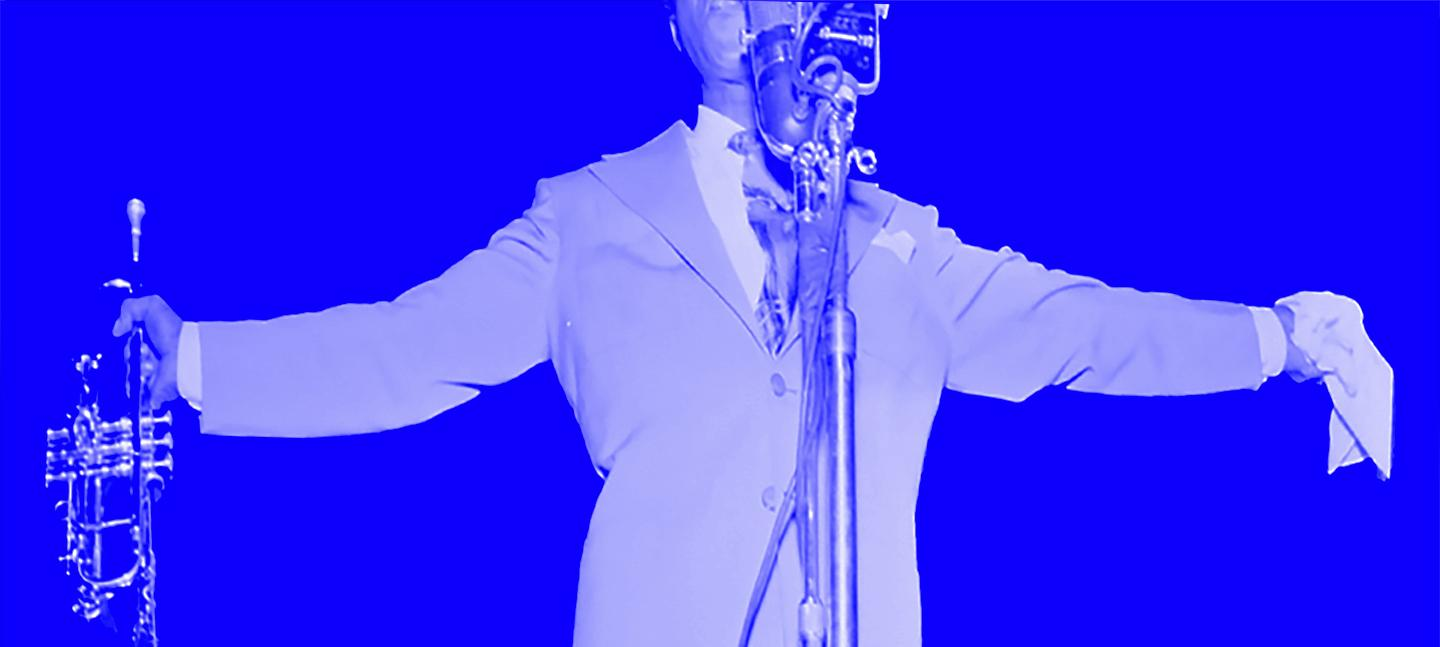 A photo of a musician with a trumpet in one hand and a handkerchief in the other, arms out, stood in front of a microphone
