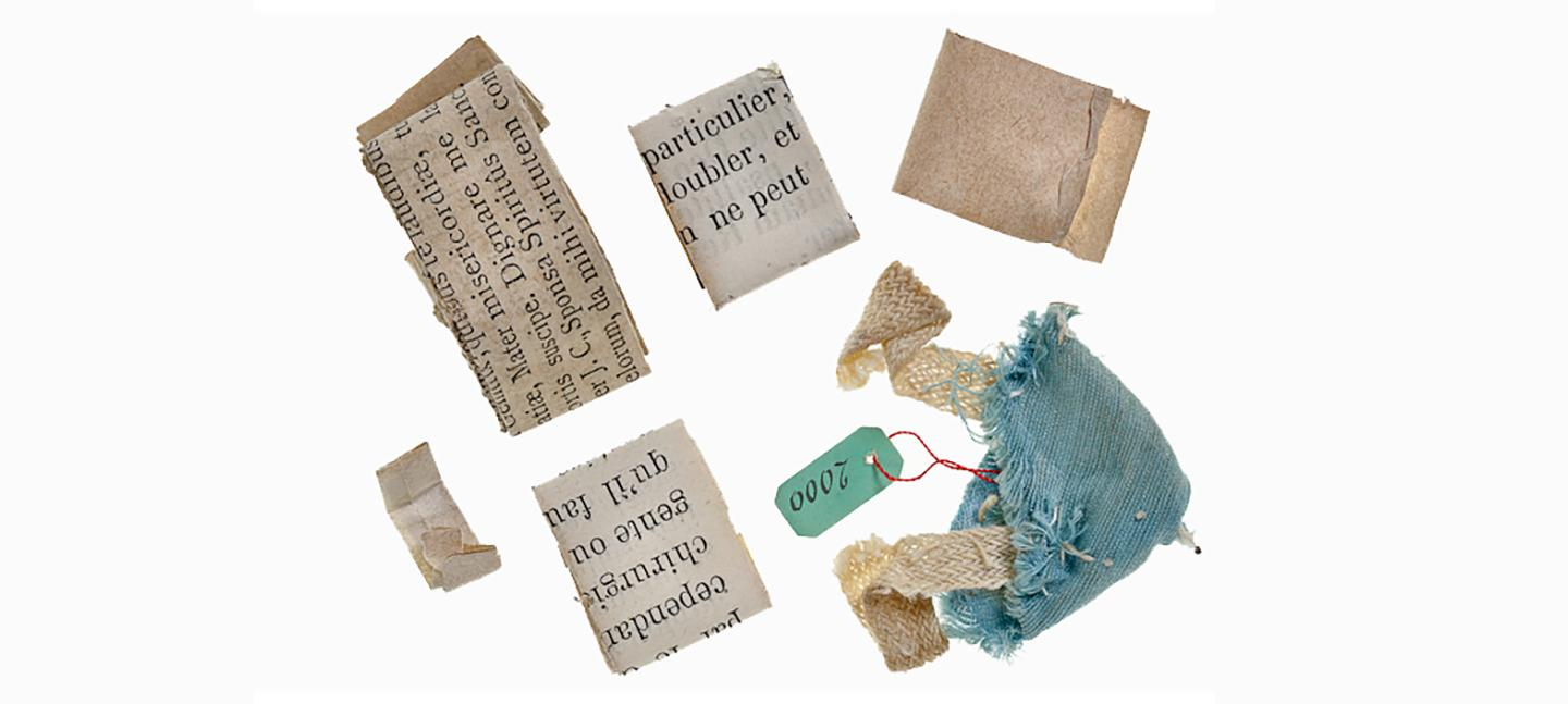 A photo of scraps of paper, folded neatly with typed French letters on them, alongside a scrap of turquoise fabric.