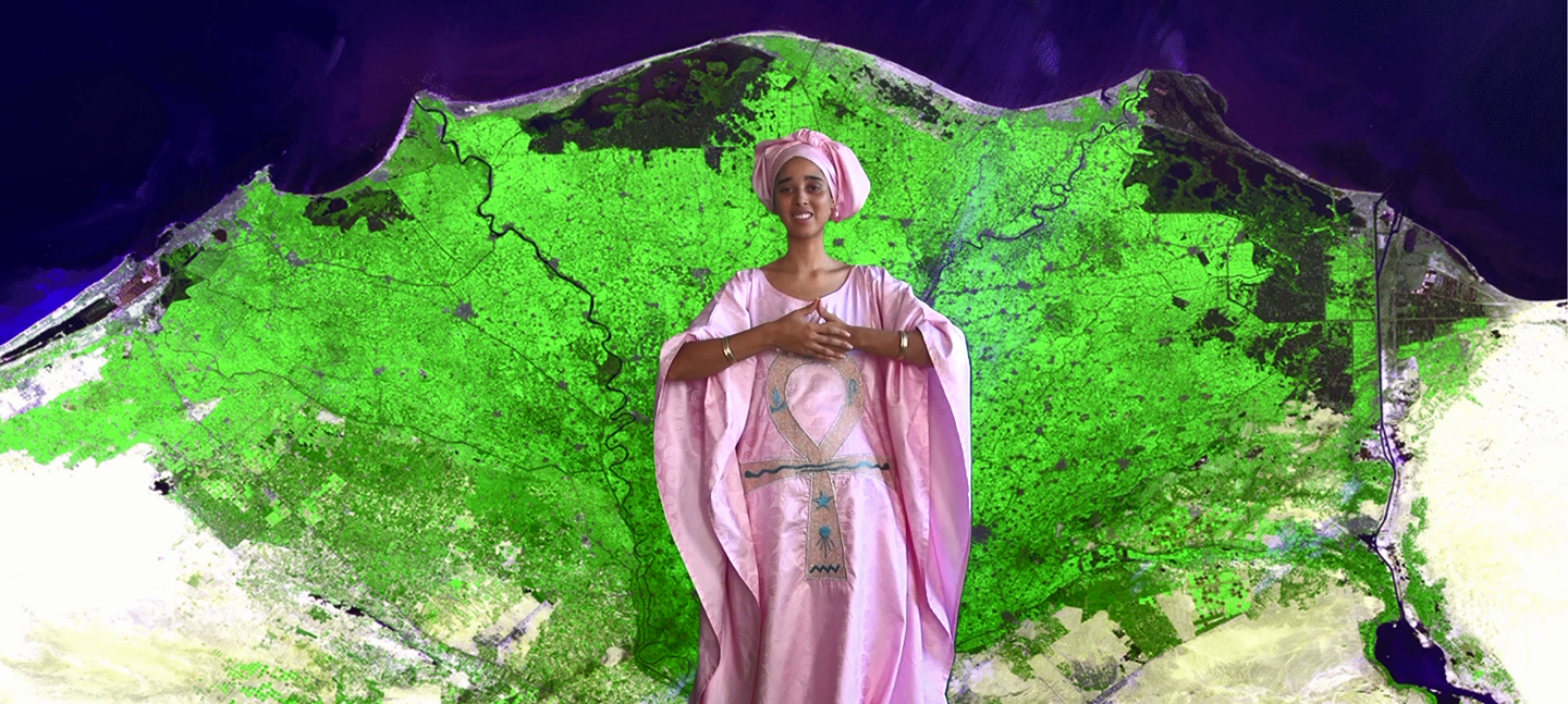 A still from Tabita Rezaire's MerKaBa for the Hoeteps, Tabita stands in a flowing pink, satin gown and head wrap, against a digital backdrop of a green aerial view of land mass and the deep blue of sky.