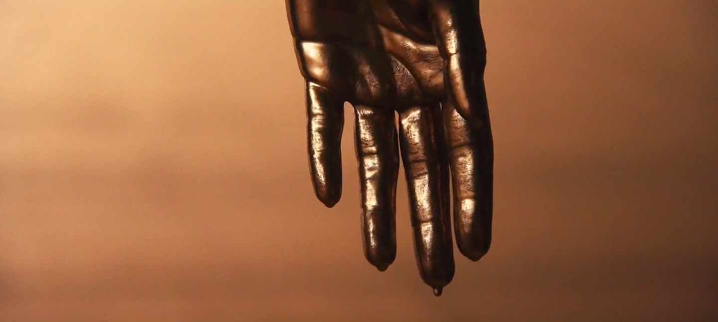 Still from Next Round, 2020, short film, collaboration between Sophia Al- Maria, Tosh Basco, Wu Tsang, with music by their long-time collaborator Patrick Belaga. A  hand drips with metallic paint.