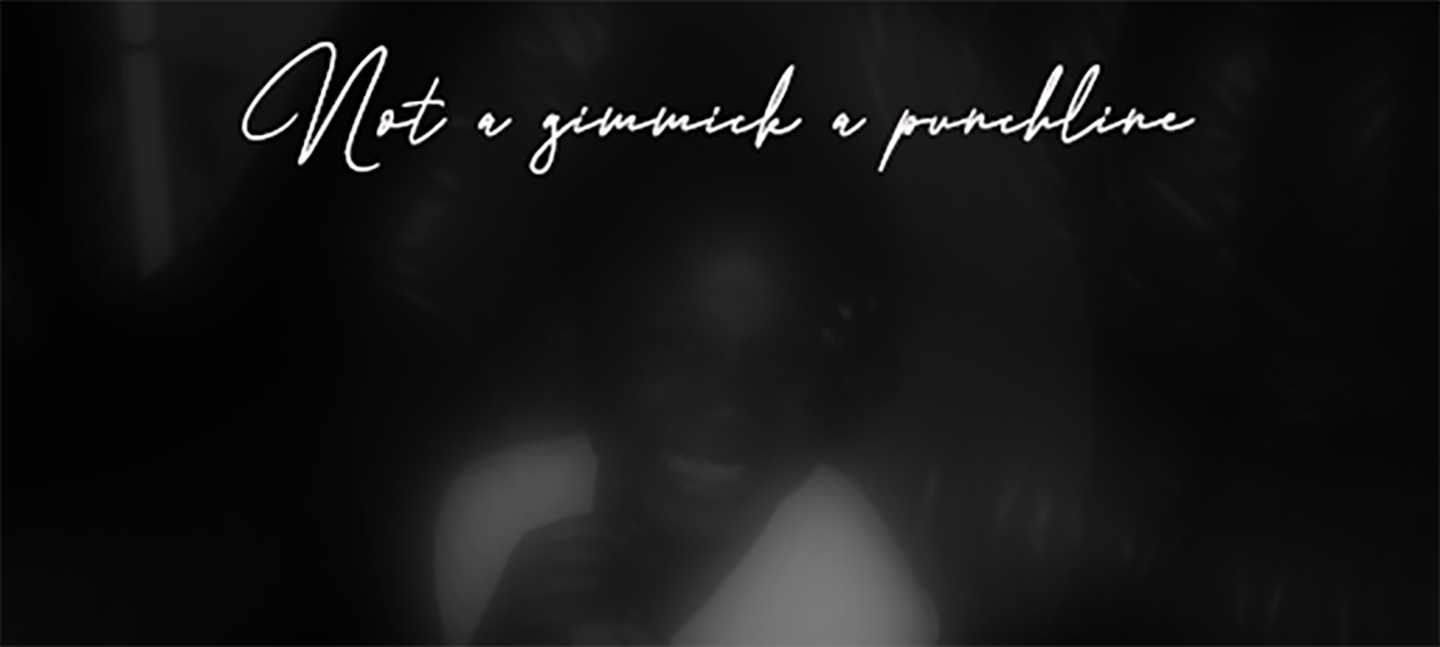 A black and white image of a blurred face wearing a white t-shirt and smiling. Above the image are the words 'Not a gimmick a punchline' in cursive writing