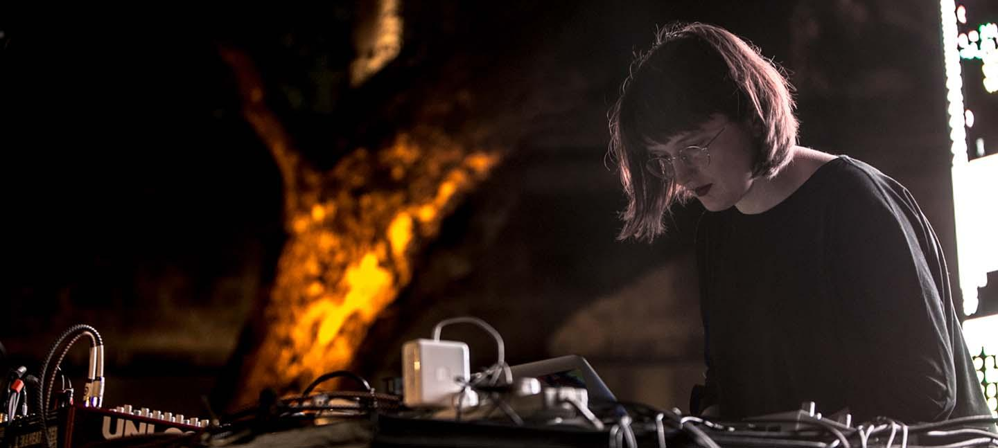 Joanne stands behind a table with a laptop and other electronic music equipment, performing.