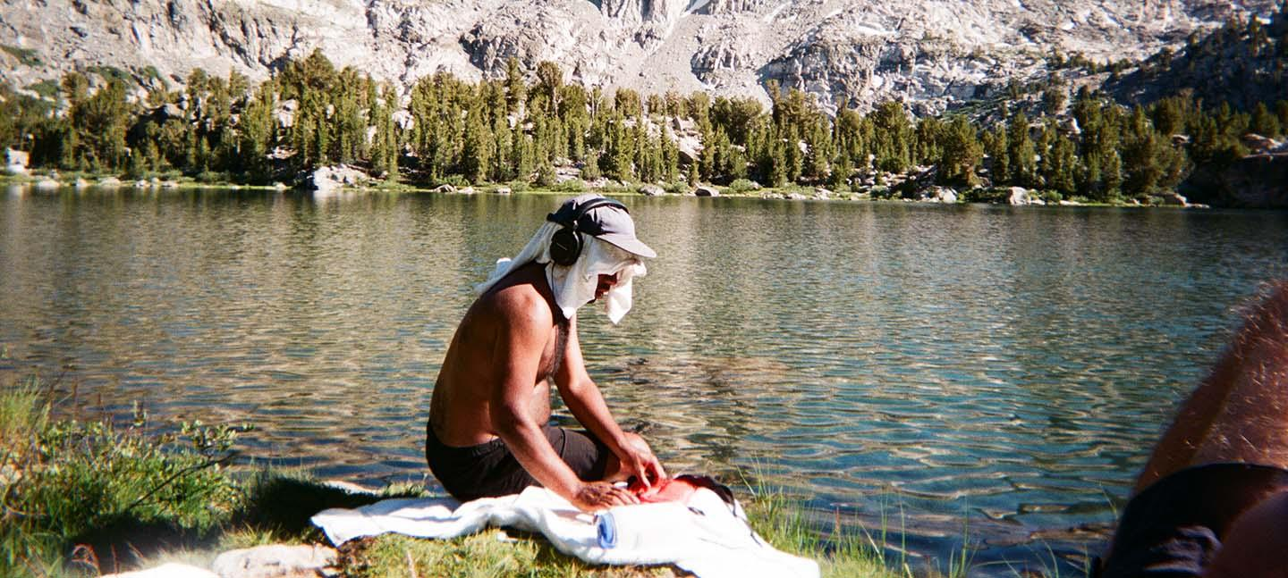 A man sits by a body of water with headphones on