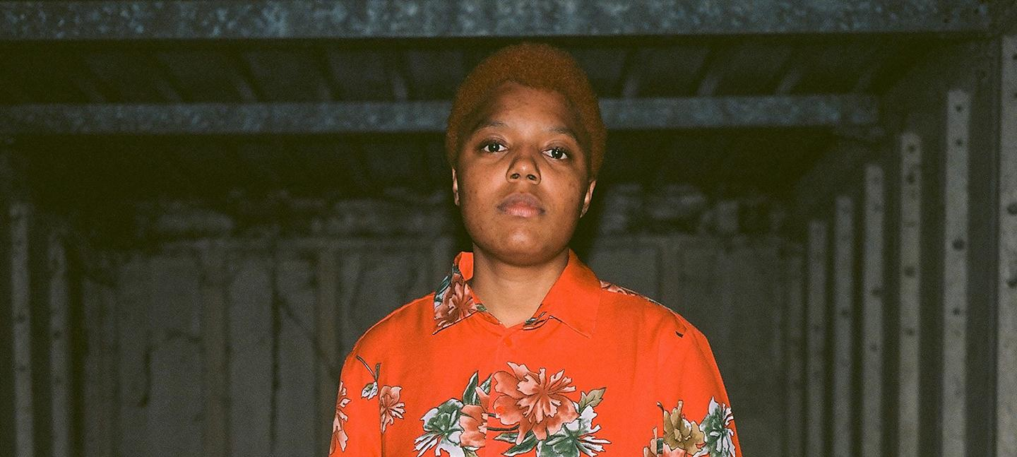 A photo of Loraine James. They wear a red shirt with hawaiian flowers on it.