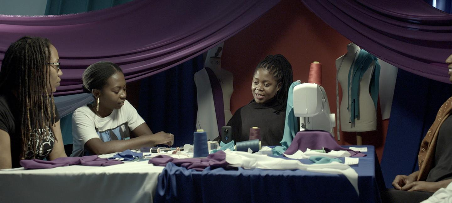 Artist Mary Sibande sitting in a textile studio talking to three women about her work