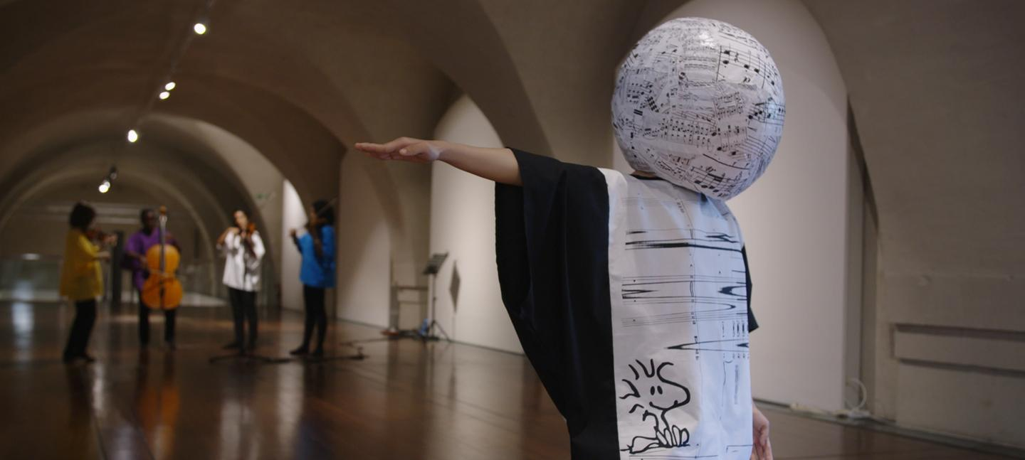 A still from Mira Calix's film 'if or unless?'. There is 1 person dancing and 4 people playing instruments in the background