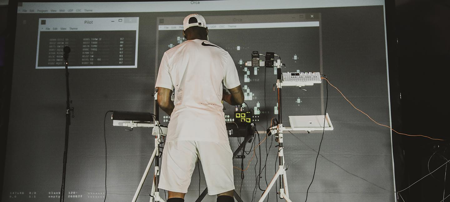 The producer NSDOS plays on stage. His back is to the camera and he stands in front of electronic music gear.