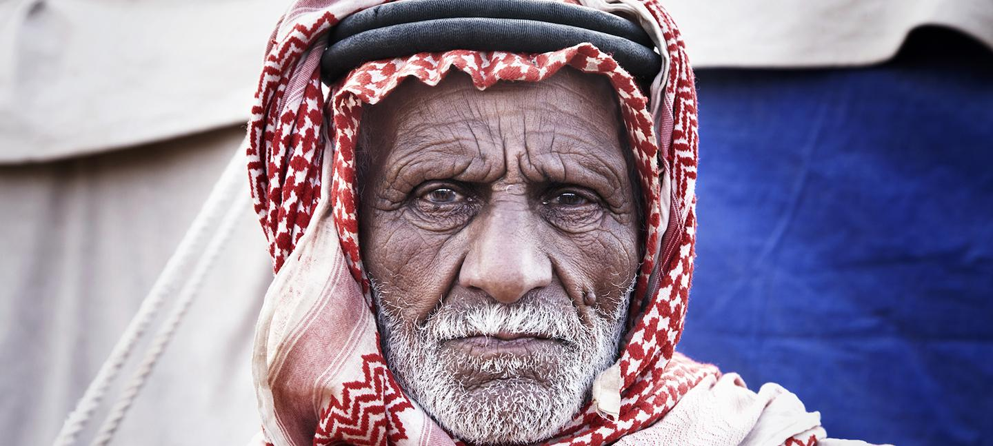 A photo of an old man wearing a head dress, looking straight into the camera, frowning slightly.