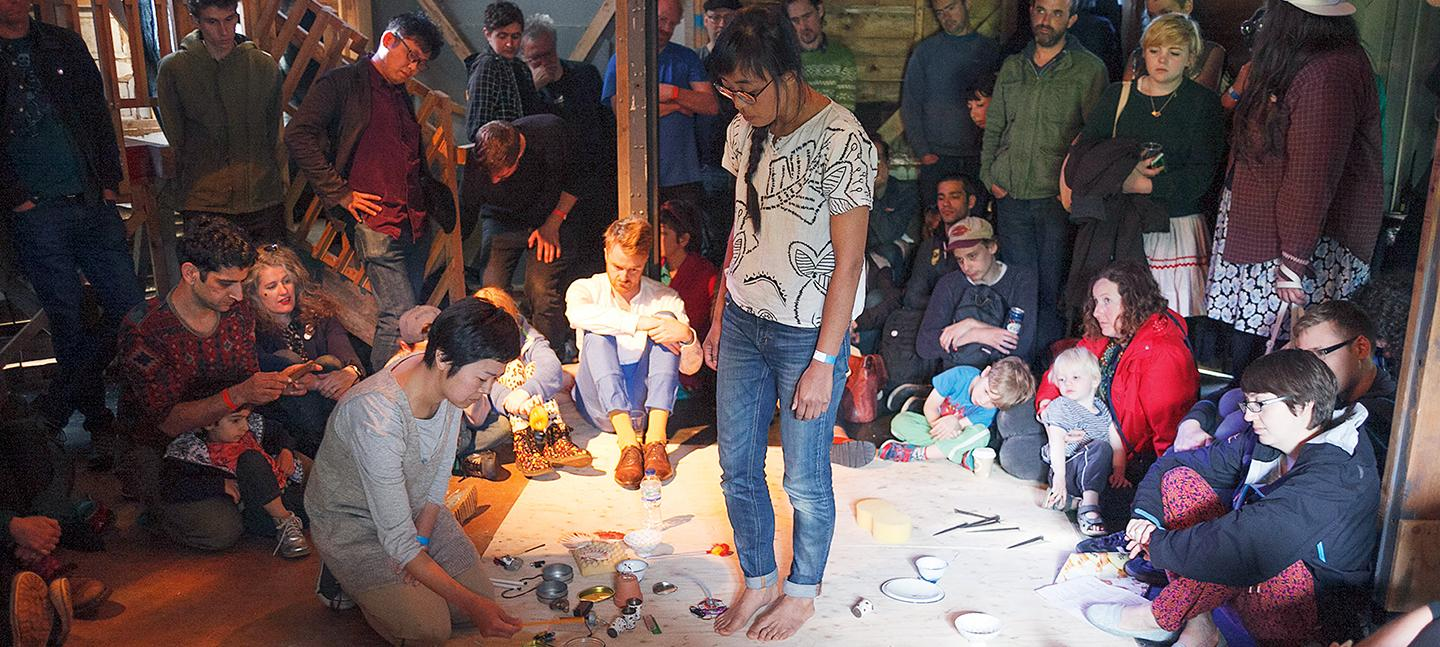 A photo of O YAMA O performing. A pair of slender young people, one kneeling, the other stood, are both atop a big sheet of paper, with bowls, cups and plates scattered between them. They are surrounded by a crowd of people who are watching on.