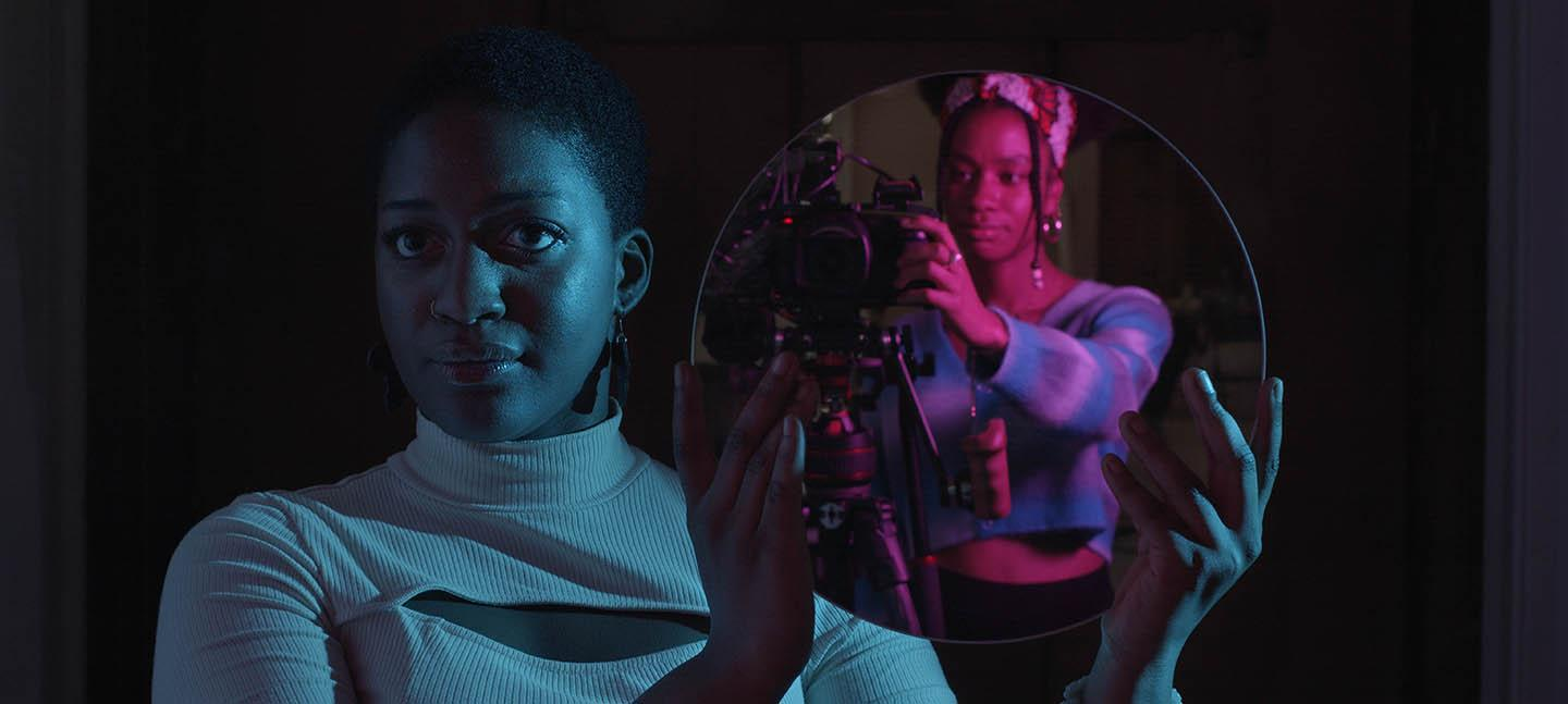A still from the Future Producers' film Rising: A Manifesto. A Future Producer, Kayleigh, holds a circular mirror up to the camera. In the reflection you can see another Future Producer, Jahnavi, operating the camera capturing the image.