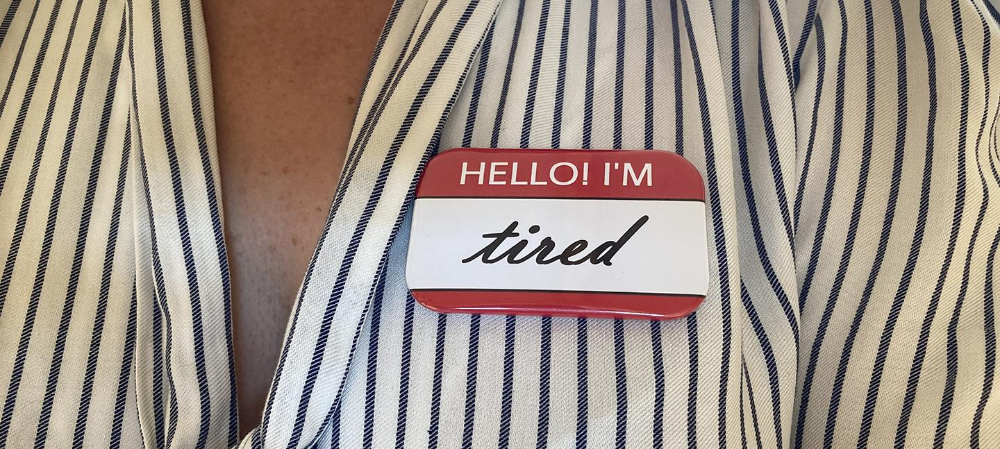 A photo of a person's upper chest, with a sticker on it that reads 'Hello! I'm tired'