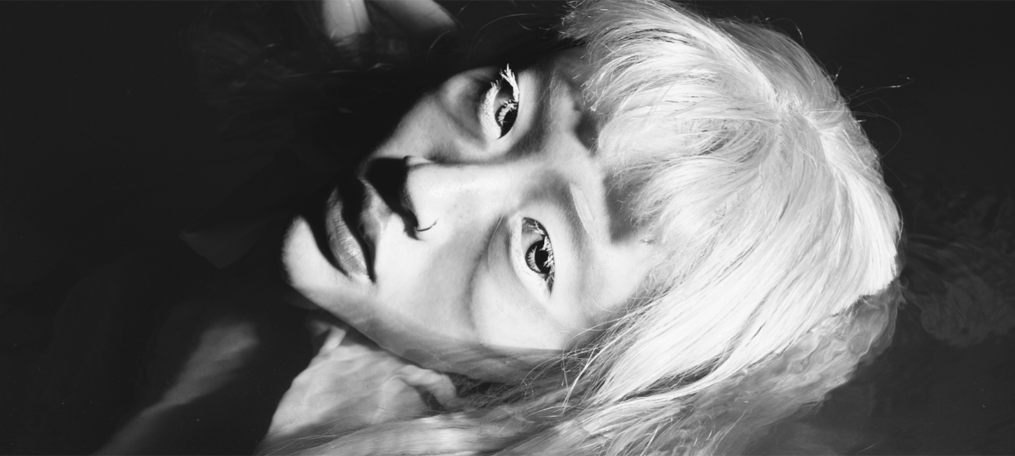 A black and white photo of the artist Yeule. They have light, straight hair with a fringe and wear a nose ring. The camera is positioned looking down, as the person looks up to the camera.
