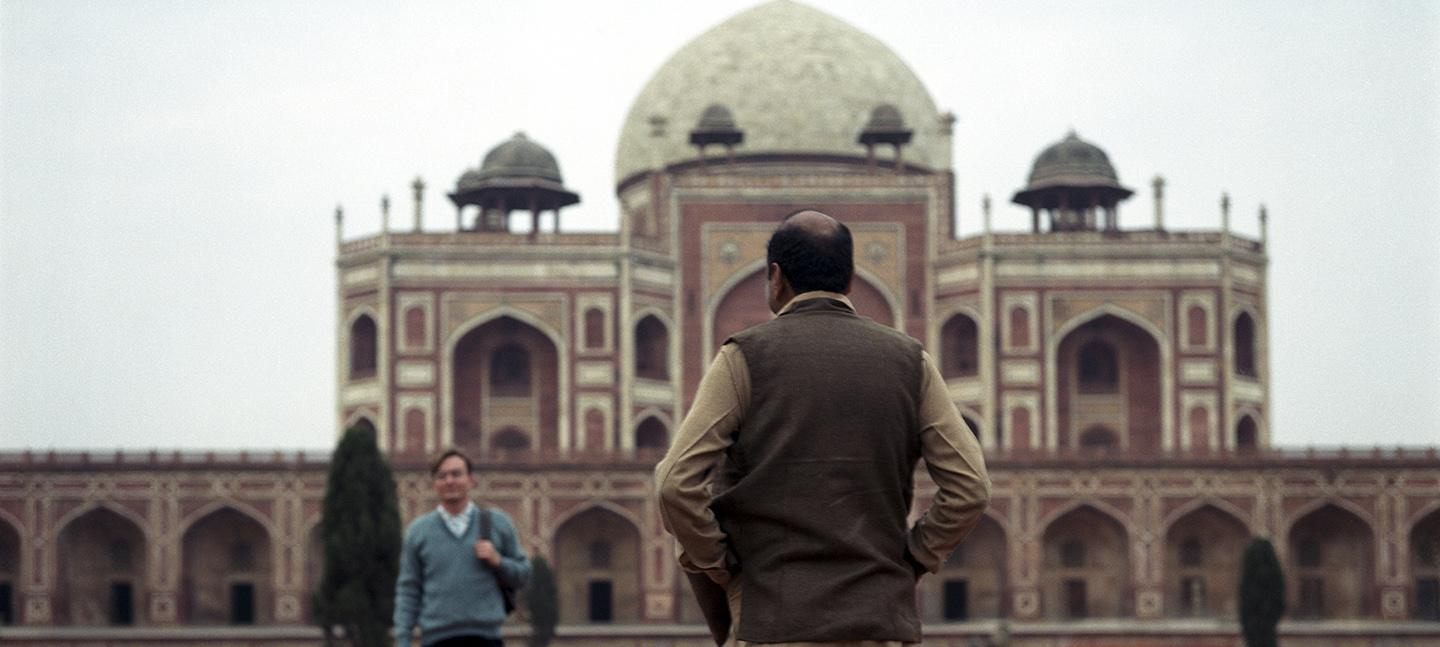 A photo by Sunil Gupta. It shows a man standing infront of a Humayun's Tomb.