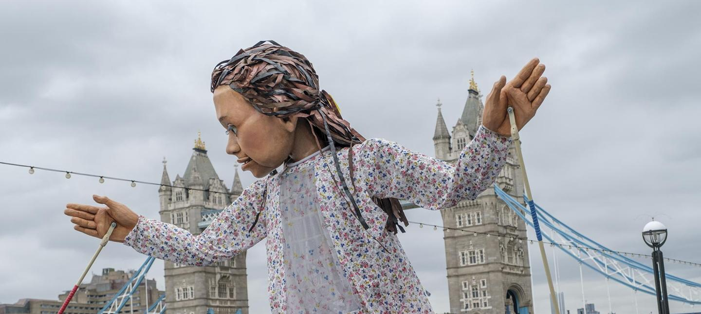 A photo of Little Amal, walking alongside the River Thames. In the background you can see Tower Bridge. The puppet looks to its right, with her hands held up and apart.
